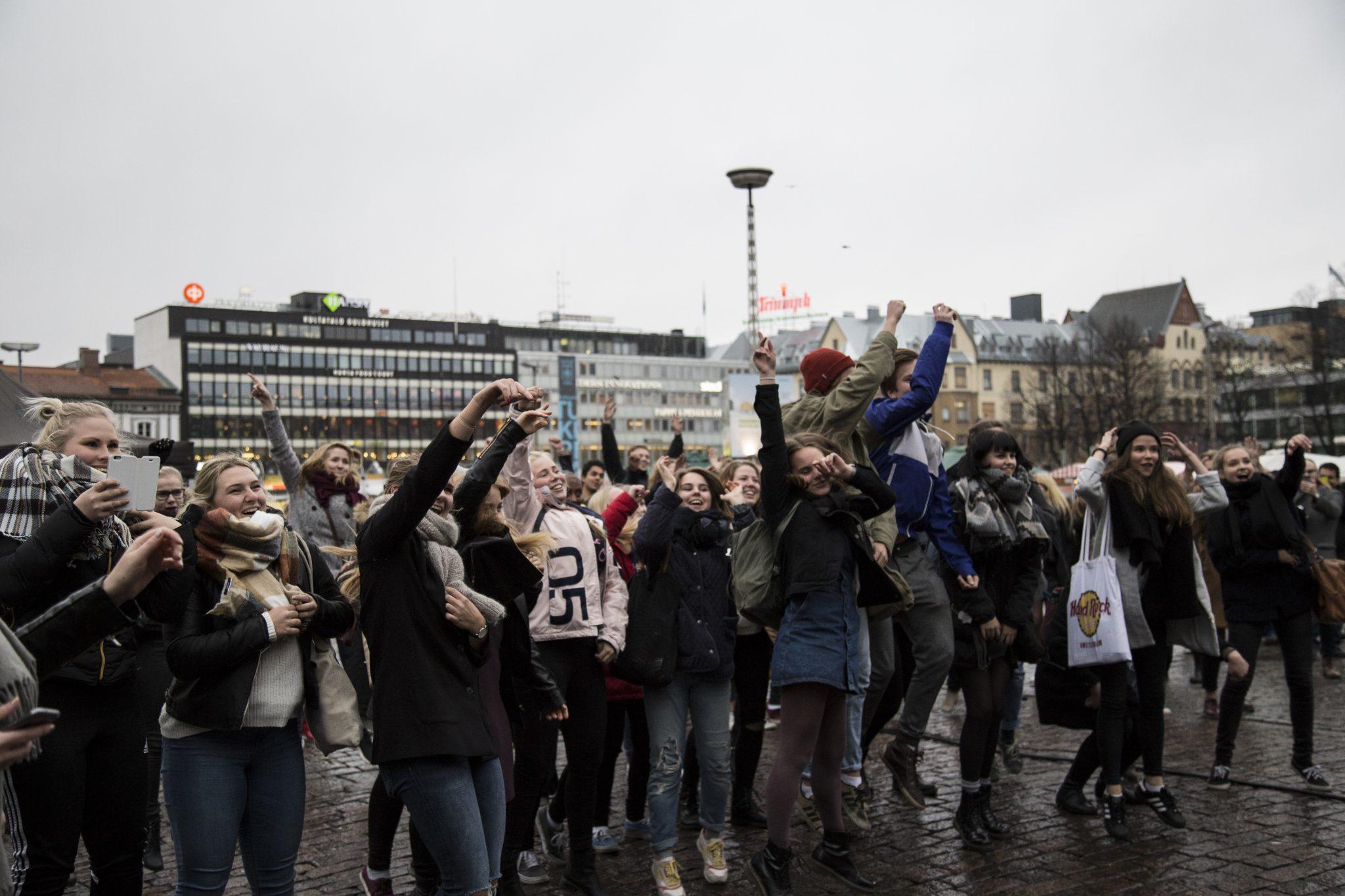 Ihmiset hyppivät ja tanssivat Turun torilla.