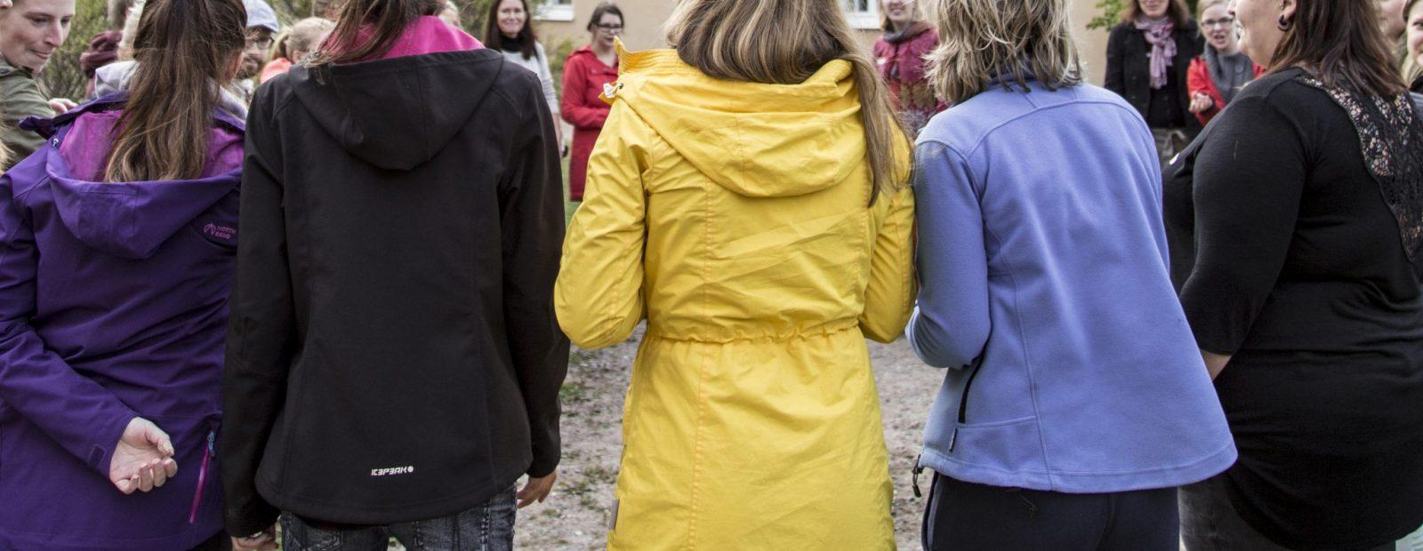 Ihmisiä selkäpäin kameraan päin, leikkivät piirileikkiä.