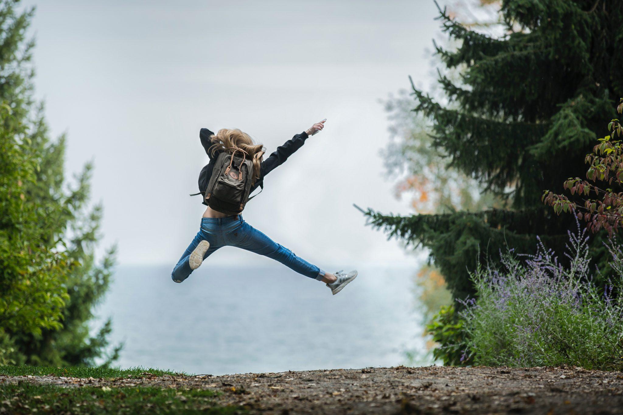 Nainen hyppää ilmaan metsäpolulla.