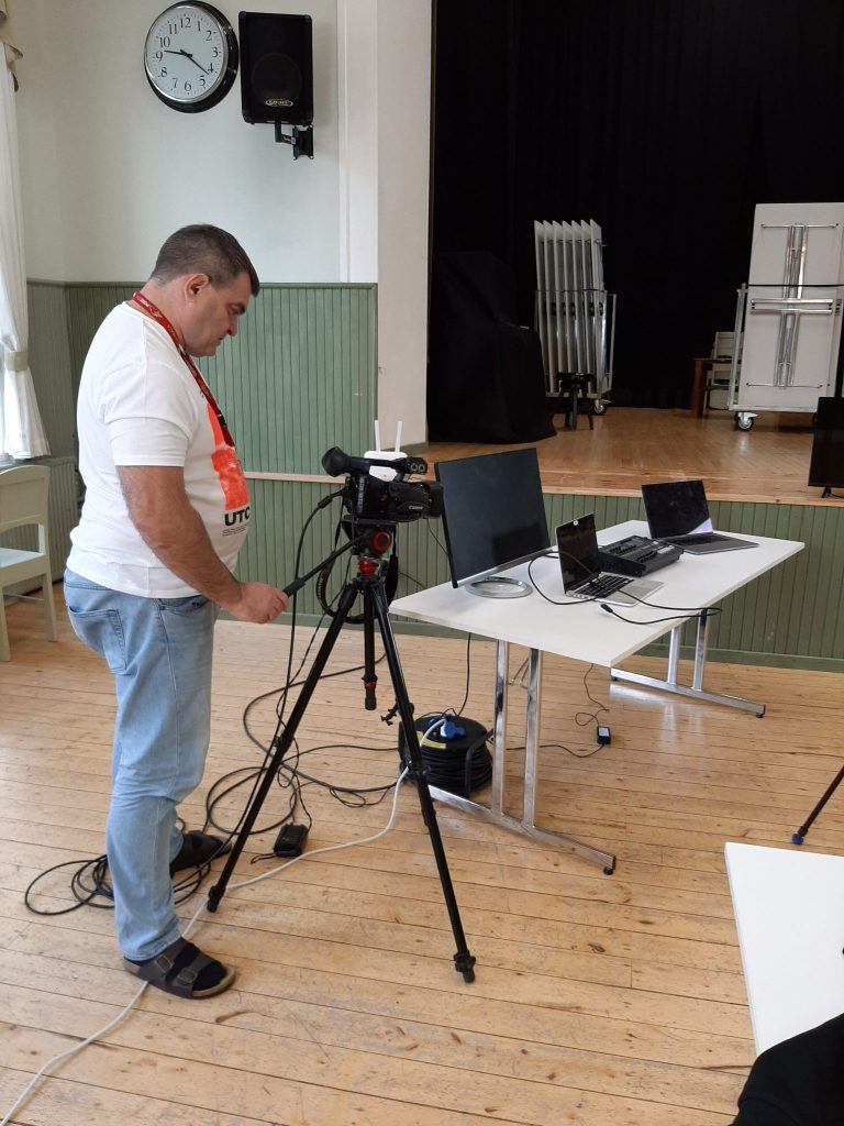 Kari Keuru seisoo videokameran vieressä ja säätää sopivaa kuvakulmaa. Kameran vieressä pöydällä kaksi tietokonetta ja yksi näyttö. Kuvassa näkyy myös osa esiintymislavasta, joka on korkeammalla kuin lattia.