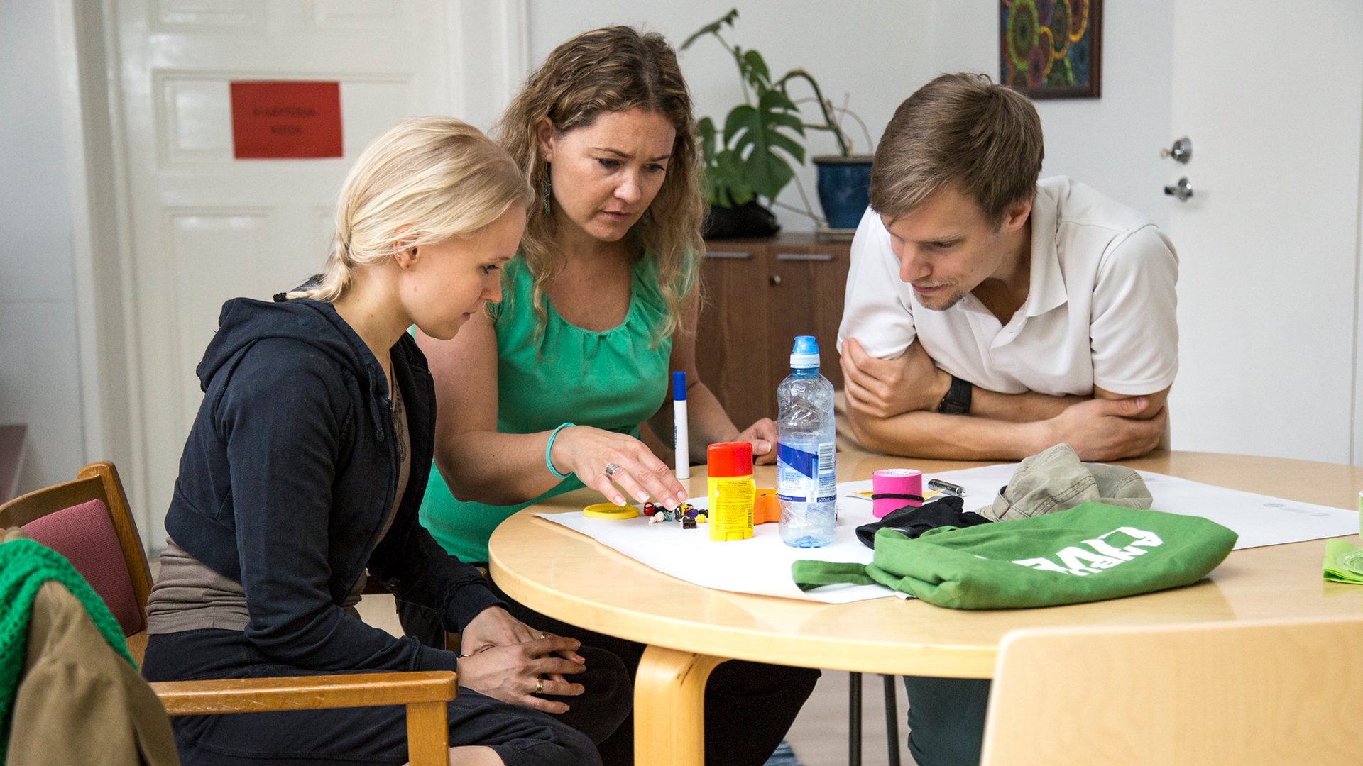 Kolme henkilöä istuu pöydän äärellä ja suunnittelee.
