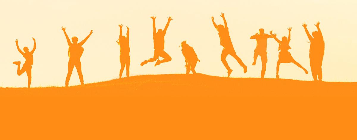Ihmiset hyppivät kukkulan päällä.