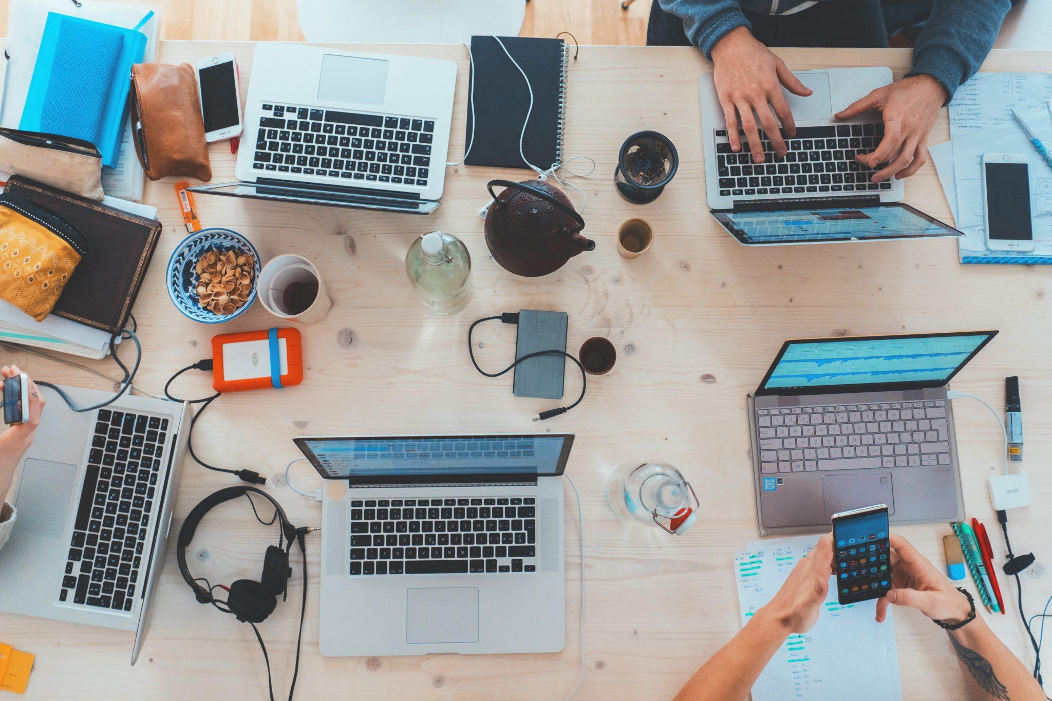 Ihmisiä työpöydän äärellä, paljon tietokoneita ja puhelimia.